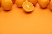 zralé šťavnaté celé a řezané pomeranče na barevném pozadí