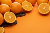 čerstvé šťavnaté pomeranče na řezací desce na barevném pozadí