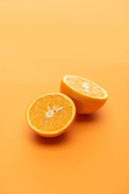 Ripe juicy orange halves on colorful background stock vector