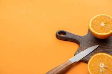 Fresh juicy orange halves on cutting board with knife on colorful background stock vector