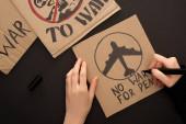 oříznutý pohled na ženu kreslení plakátu bez války za mír písmo a letadlo na černém pozadí