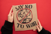 částečný pohled na ženu držící kartonový štítek s nápisem žádná válka s válečným písmem a výbuchem v stopce na červeném pozadí