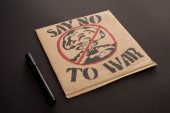 značka v blízkosti lepenkový plakát s říci ne na válečné písmo a výbuch v stop znamení na černém pozadí