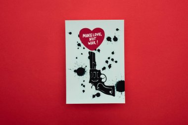 Top view of white paper with drawn black revolver and heart with make love not war lettering on red background stock vector