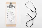 koláž schránky s probiotiky prázdný seznam s pilulky a stetoskop na bílém pozadí