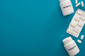 top view of containers with probiotic lettering, pills and blister pack on blue background