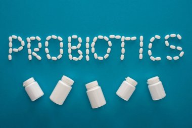 Top view of probiotics lettering made of pills and white containers on blue background stock vector