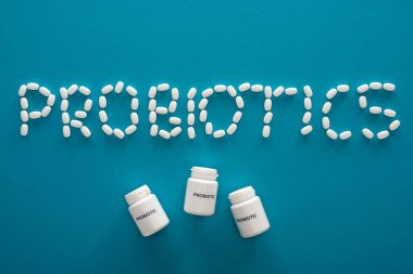 Top view of probiotics lettering made of pills and containers on blue background stock vector