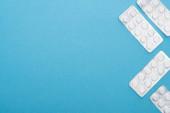 Ansicht von Pillen in Blisterverpackungen auf blauem Hintergrund