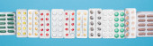 horní pohled na barevné pilulky v blistrech balení na modrém pozadí, panoramatická orientace