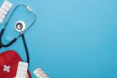 Ansicht von Pillen in Blisterverpackungen, Verbandskasten und Stethoskop auf blauem Hintergrund