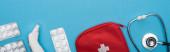 top view tabletták buborékcsomagolásban, sztetoszkóp, elsősegély készlet és fül hőmérő kék alapon, vízszintes kép