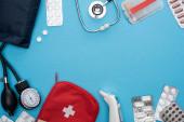 horní pohled na ušní teploměr, pilulky v blistrech, sfygmomanometr, lékárnička a stetoskop na modrém pozadí
