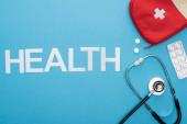 vrchní pohled na stetoskop, pilulky v blistru balení, lékárnička a zdravotní nápisy na modrém pozadí