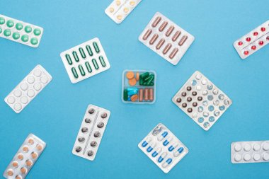 Top view of colorful pills in blister packs and plastic container on blue background stock vector