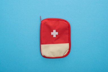 Top view of red first aid kit on blue background stock vector