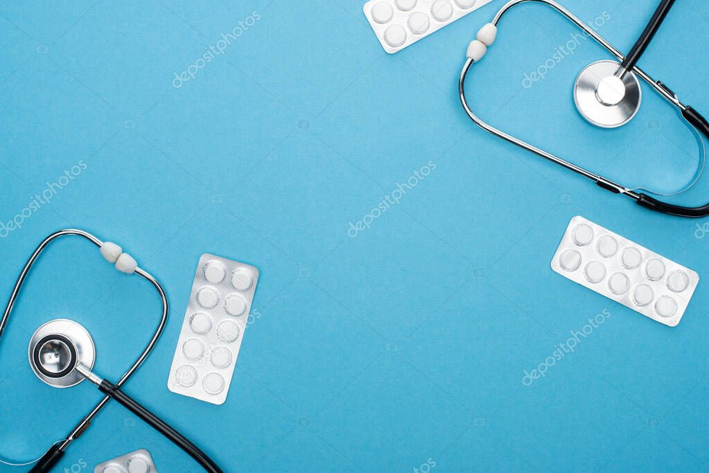 Top view of pills in blister packs and stethoscopes on blue background stock vector