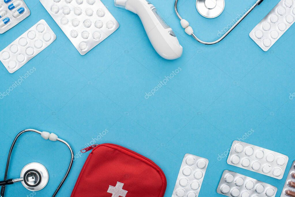 Top view of pills in blister packs, stethoscopes, first aid kit and ear thermometer on blue background stock vector