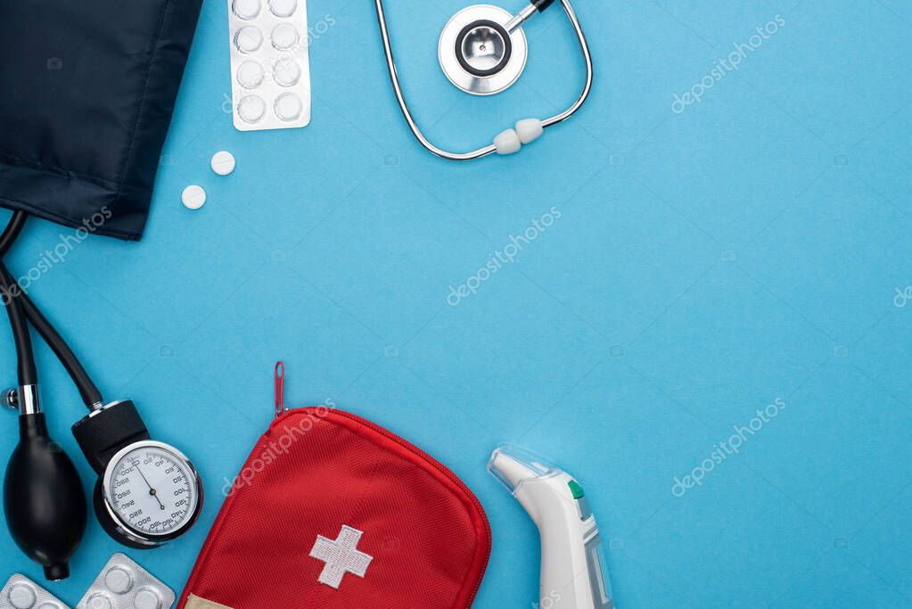 Top view of ear thermometer, pills in blister packs, sphygmomanometer, first aid kit and stethoscope on blue background stock vector