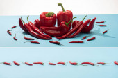 collage of fresh red bell peppers and chili on blue surface on white background