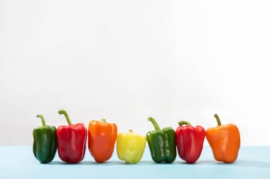 Fresh colorful bell peppers in row on blue surface on white background stock vector