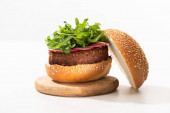 delicious vegan burger with radish and arugula on wooden board on white background