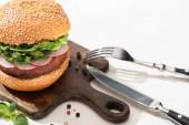 selektivní zaměření lahodného veganského burgeru s ředkvičkou a rukolou na dřevěné desce s černým pepřem u vidličky a nožem na bílém pozadí