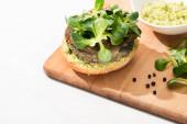 szelektív fókusz finom zöld vegán burger mikrozöldek és püré avokádó fa vaddisznó fekete bors fehér háttér