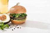 Fotografie vynikající zelený veganský burger s mikrozelení, avokádo, černý pepř na bílém pozadí