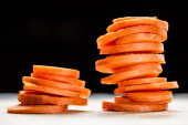 close up view of fresh ripe carrot slices isolated on black