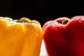 zblízka pohled na čerstvé zralé papriky s kapkami vody izolované na černé