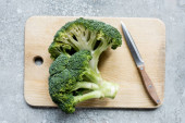top view of fresh green cut broccoli on wooden cutting board with knife on grey surface