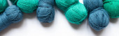 top view of blue and green wool yarn on white background, panoramic orientation