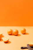 ripe fresh oranges and wooden cutting board isolated on orange