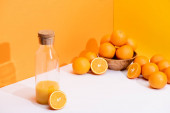 fresh orange juice in glass bottle near ripe oranges in bowl on white surface on orange background