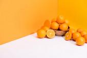 frische reife Orangen in Schale auf weißer Oberfläche auf orangefarbenem Hintergrund