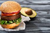 selektiver Schwerpunkt leckerer veganer Burger mit Rettich auf Holztisch mit Avocadohälfte
