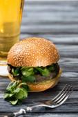 selektivní zaměření chutného veganského burgeru s mikrozelení podávaného na dřevěném stole se sklenicí piva a vidličkou