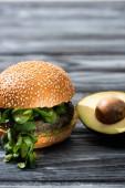 chutný veganský burger s mikrozelení podávaný na dřevěném stole s avokádovou půlkou