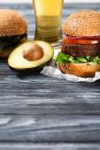 Leckere vegane Burger auf Holztisch mit Bier und Avocado