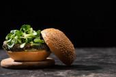 chutný veganský burger s mikrozelení podávaný na dřevěné desce izolované na černé