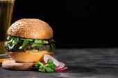 selektivní zaměření chutného veganského burgeru s mikrozelení podávané s pivem a ředkvičkami na texturovaném povrchu izolovaném na černém