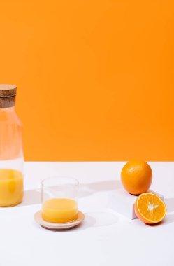 Fresh orange juice in glass and bottle near oranges on white surface isolated on orange stock vector