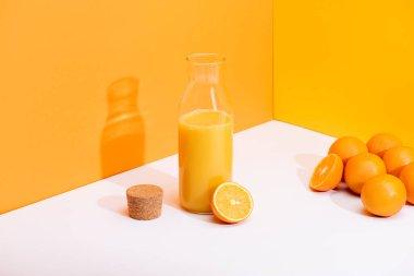 Fresh orange juice in glass bottle near ripe oranges and cork on white surface on orange background stock vector