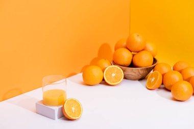 Fresh orange juice in glass near ripe oranges in bowl on white surface on orange background stock vector