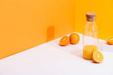 Fresh orange juice in glass bottle near ripe oranges on white surface on orange background stock vector