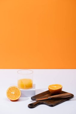 Fresh orange juice in glass near cut fruit on wooden cutting board with knife on white surface isolated on orange stock vector