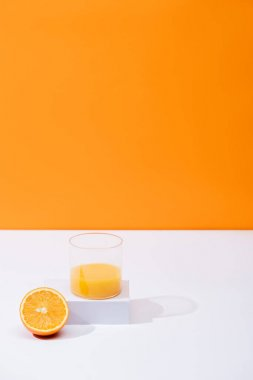 Fresh orange juice in glass near cut fruit on white surface isolated on orange stock vector