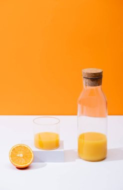 Fresh orange juice in glass and bottle with cork near cut fruit on white surface isolated on orange stock vector