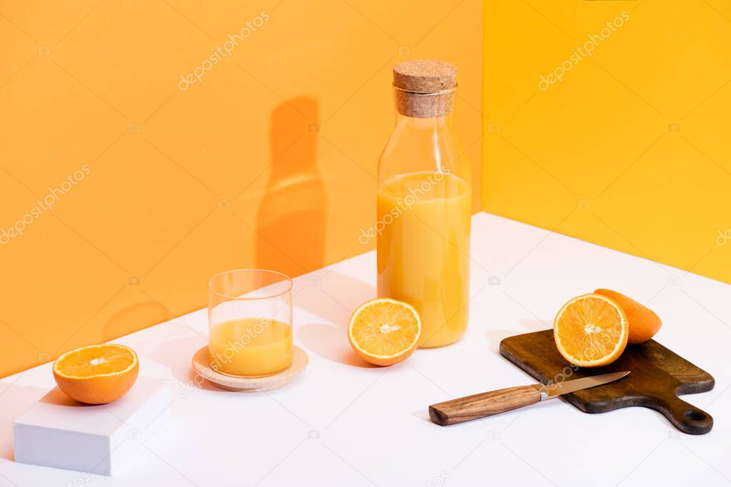 Fresh orange juice in glass and bottle near ripe oranges, wooden cutting board with knife on white surface on orange background stock vector